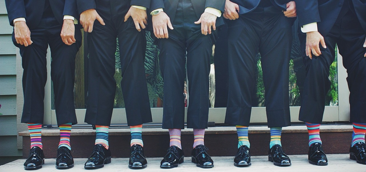 Men in suits showing off their funky socks