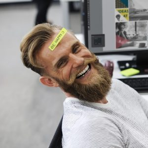 man relaxing at desk laughing on first day at a new job