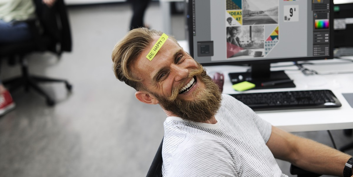 man relaxing at desk laughing with post-it note on his forehead reading 'be happy'