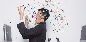 Woman in the office throwing confetti all over herself