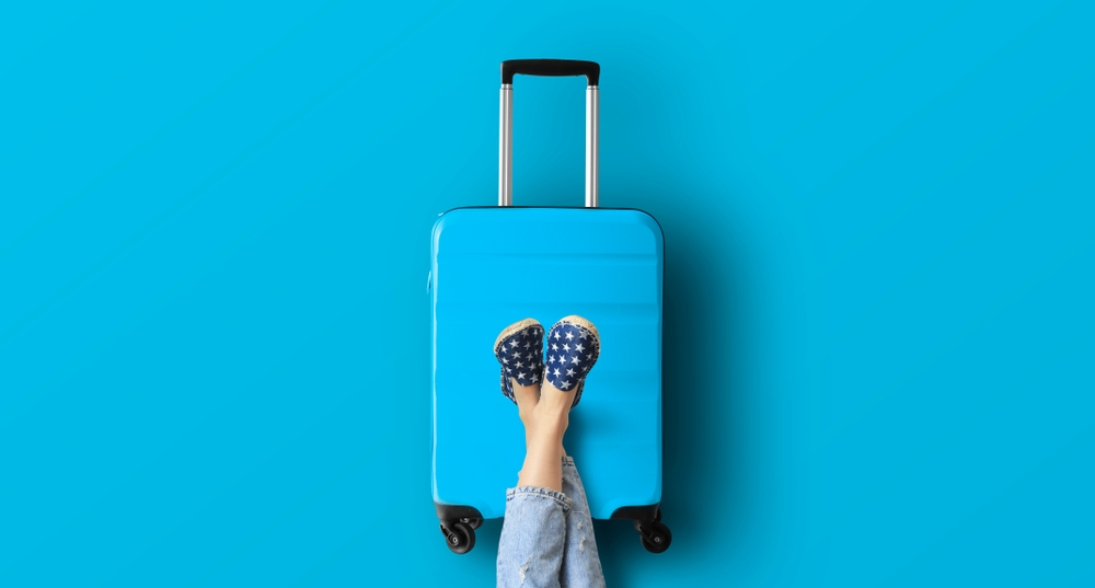 person-resting-feet-on-a-blue-suitcase-waiting-for-vacation
